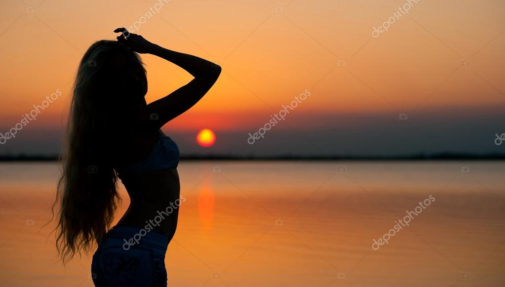Beautiful young woman silhouette at the beach at sunset.