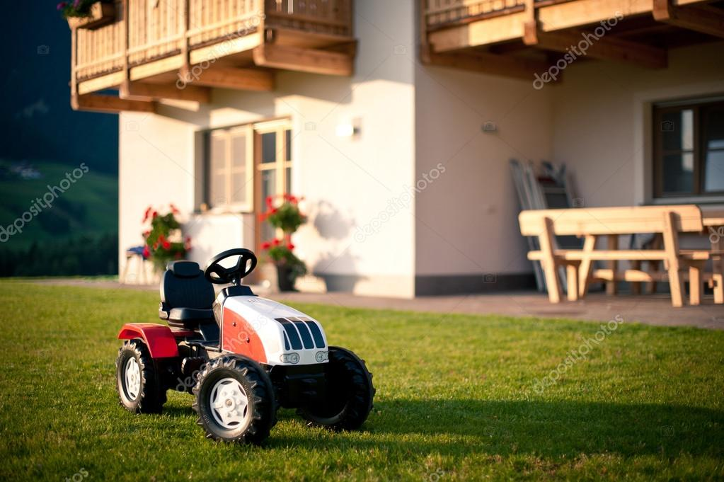 Tractor toy in front of mountain house. Dolomites, Italy.
