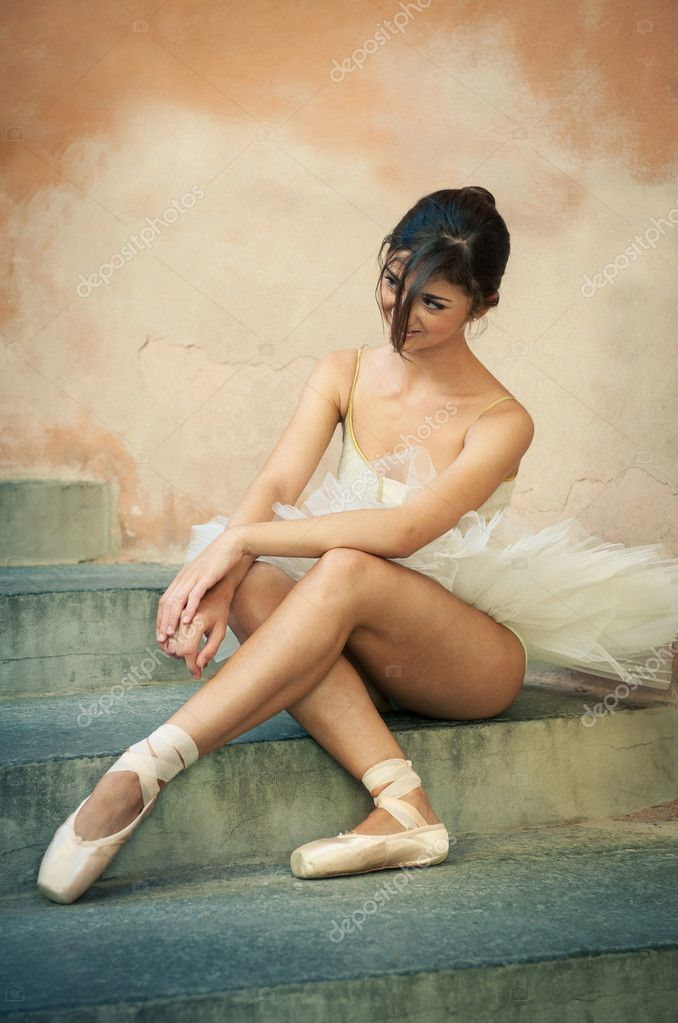 Young beautiful ballerina posing sit on the stairs. Vintage style