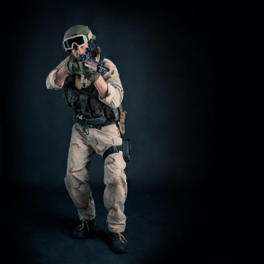Soldier with rifle against black background. Full body and copy