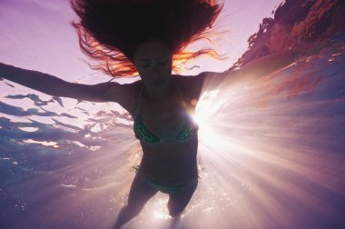Woman silhouette underwater in swimming pool with back light