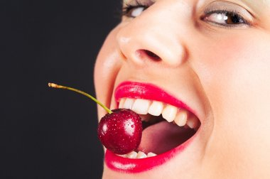 Close up portrait of beautiful young woman with cherry