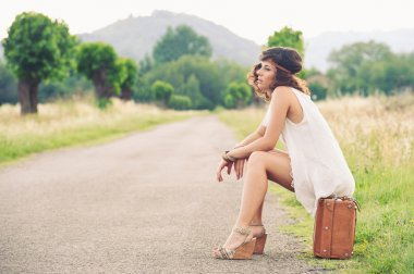 Beautiful girl waiting on a country road with her suitcase