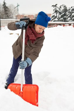 Woman shoveling snow off sidewalk