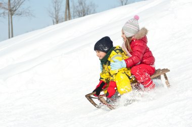 Two kids sliding with sledding in the snow