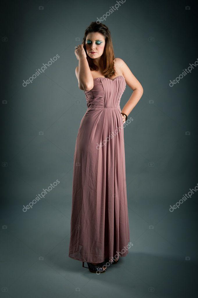 6ae7b650e5 Ritratto di una bella ragazza con vestito rosa su sfondo scuro ...