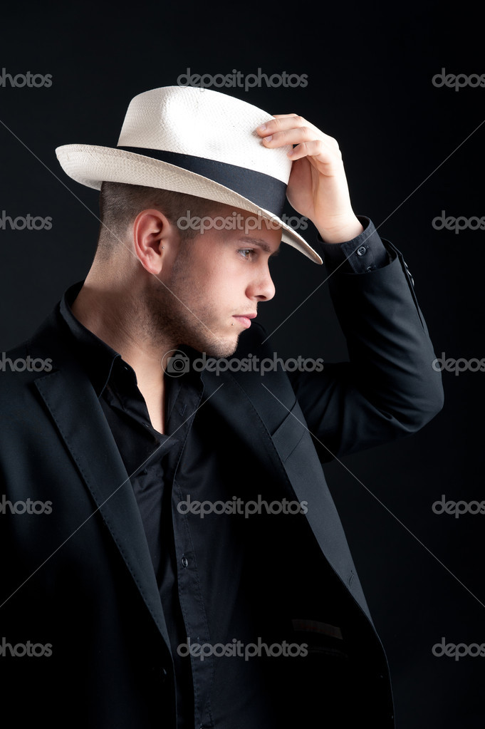 6e0966a818778 Portrait de jeune homme avec un chapeau blanc sur fond noir– images de  stock libres de droits