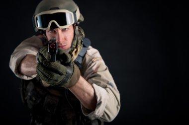 Soldier with gun against black background