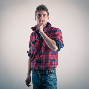 Young man with plaid shirt saying to be quiet. Studio shot