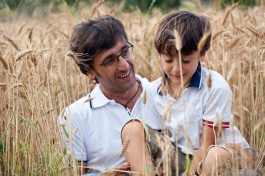 Father playing with his son in a wheat field