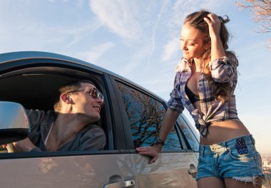 Young beautiful woman hitchhiker standing at side window and charming driver