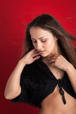 Beautiful brunette woman close up portrait against red background