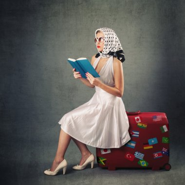 Retro woman with sunglasses and suitcase reading book portrait against grey background