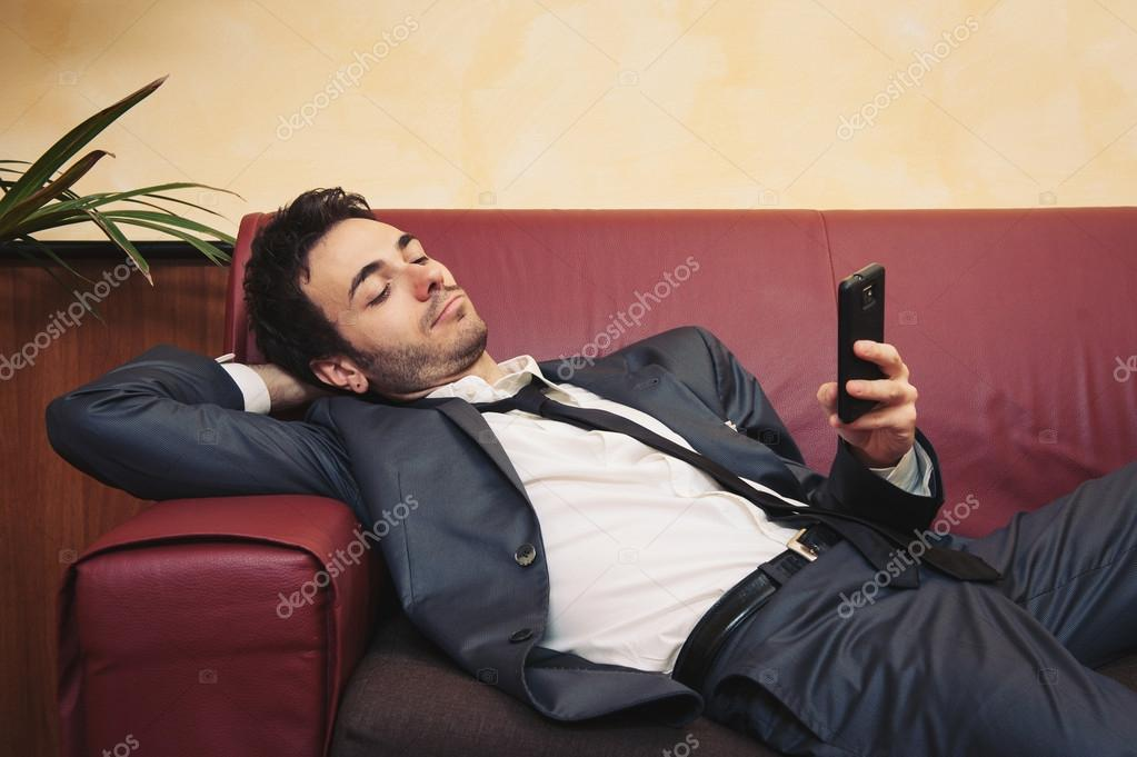 Portrait of tired young businessman typing on cellphone on sofa