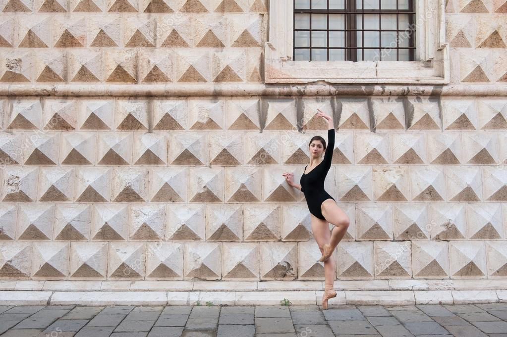 Young beautiful ballerina dancing outdoors in front of Palazzo dei Diamanti in Ferrara, Italy