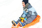 Kind rutscht mit Bob in den Schnee