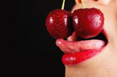 Detail of young woman mouth with cherries against black background