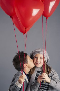 Young boy kissing girl with red heart balloons on grey background