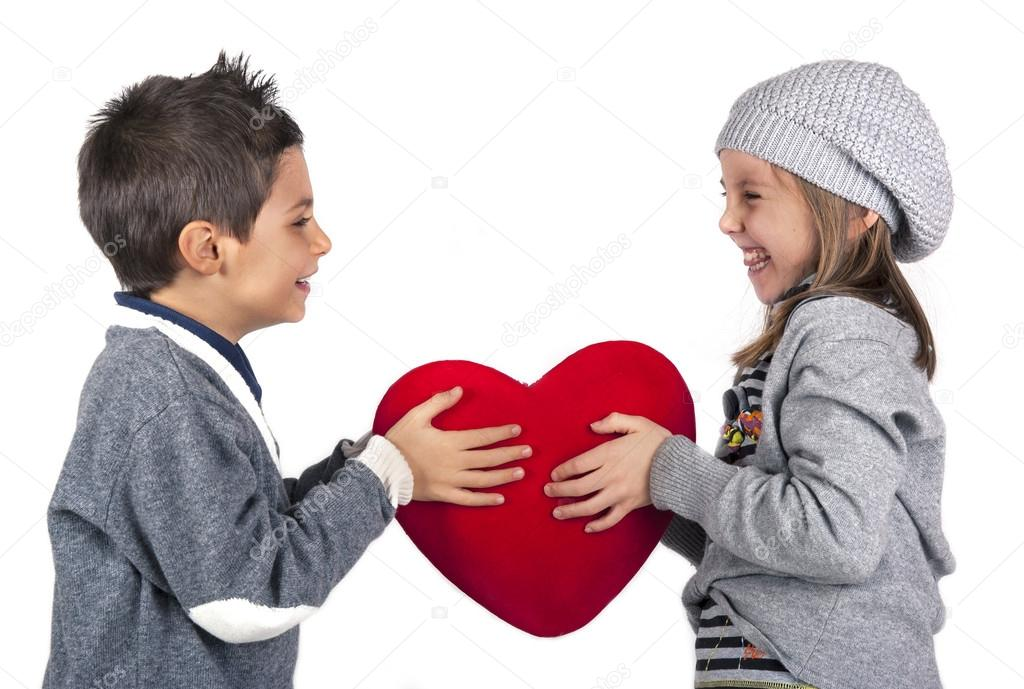 Couple of kids playing with red heart over white background. Valentines