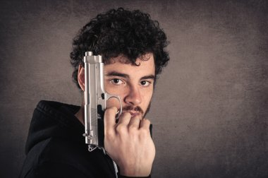 Young killer with gun portrait over grunge background.