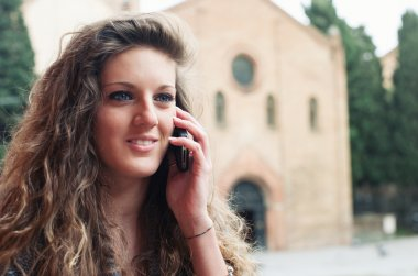 Teenager talking at mobile phone in Saint Stephen square, Bologna, Italy.