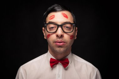 Funny portrait of young nerd with kiss imprints isolated on black background.
