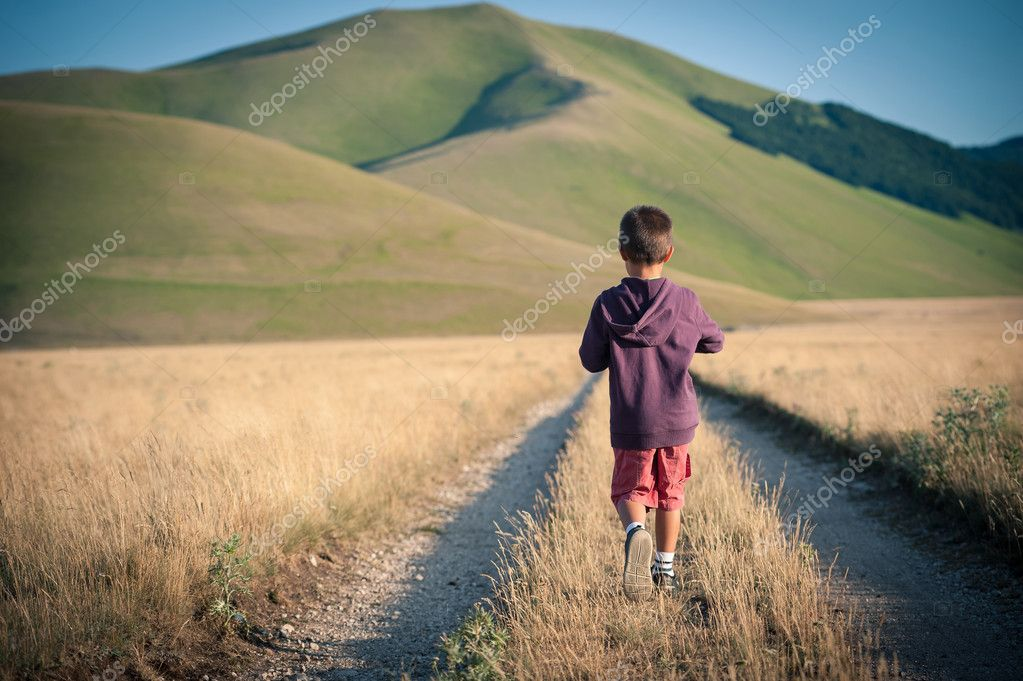 Kid walking alone outdoors. Castelluccio di Norcia, Monti Sibillini Park, Italy.