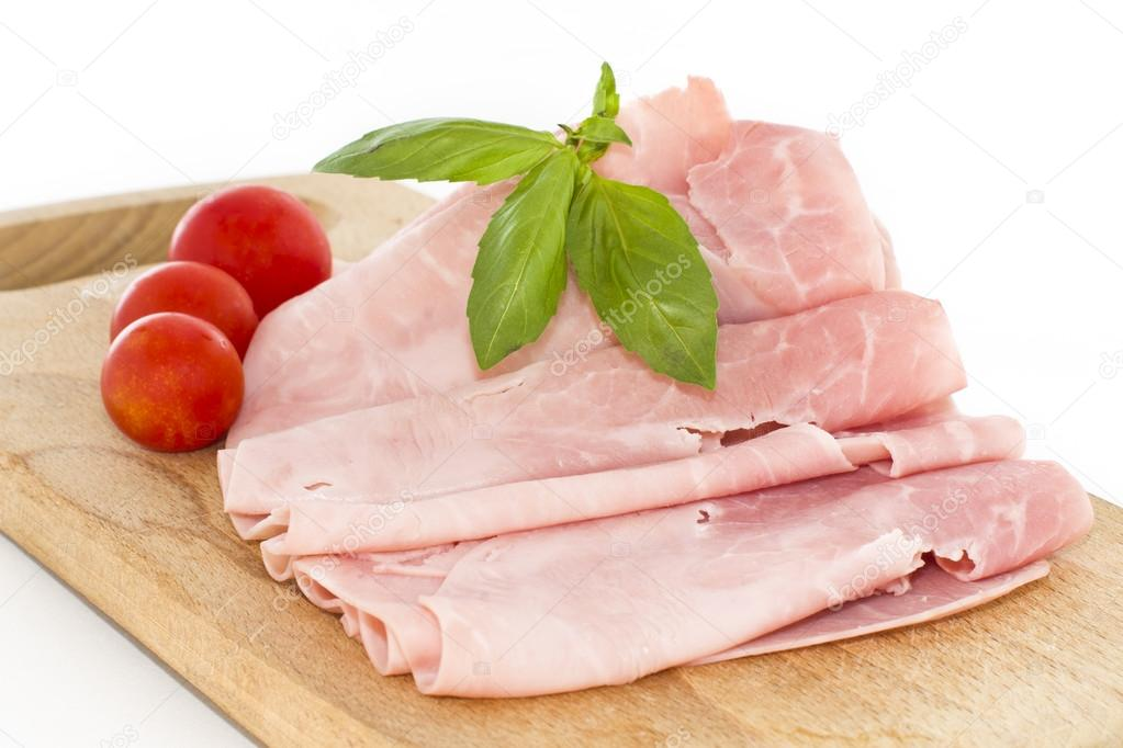 Baked ham with slices and tomatoes on wooden board