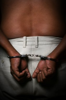 Man in handcuffs on black background