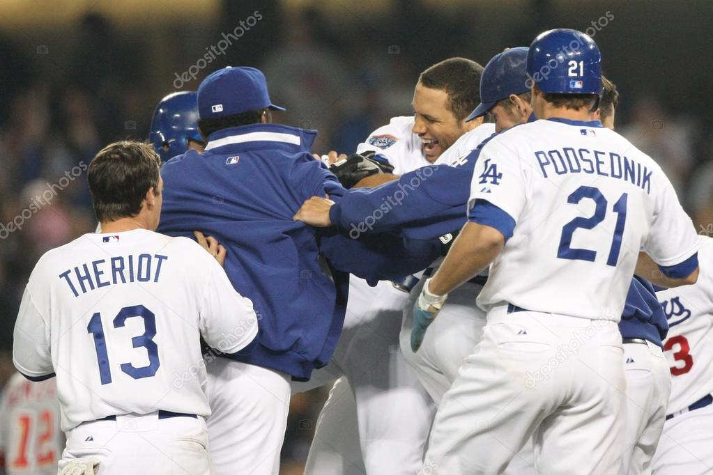 James Loney gets rushed by teammates after batting in the winning run of the game