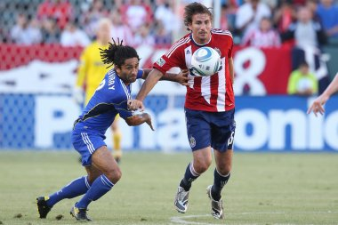Alan Gordon and Kansas City Wizards midfielder Stephane Auvray fight for the ball during the game