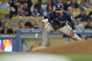 ADRIAN GONZALEZ catches a throw from third to complete an out during the game