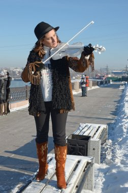 The girl with a white violin is on the bench at the winter promenade. Irkutsk
