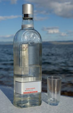 A bottle of vodka and a shotglass on the coast of Lake Baikal