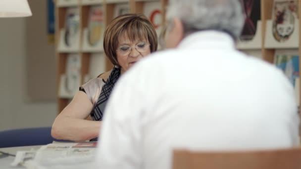 aktivní důchodce důchodci, stará žena čte papíru s manželem v rekreačním centru.