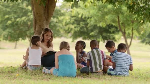 mladá žena v práci jako vychovatel čtení knih pro chlapce a dívky v parku