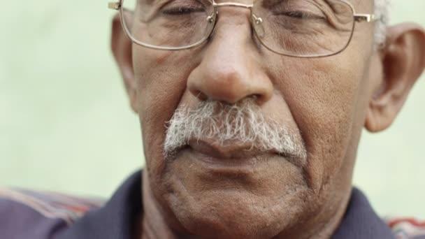Ritratto di uomo afroamericano vecchio triste con occhiali e baffi