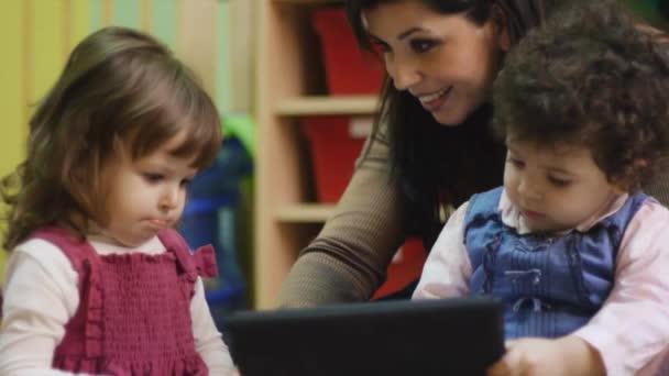 pedagog a malých holčičkách s touch pad počítač v mateřské školce