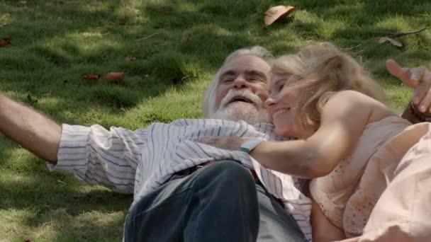 glücklicher Opa und Oma mit Enkel beim Spielen und Liegen auf Gras im Park