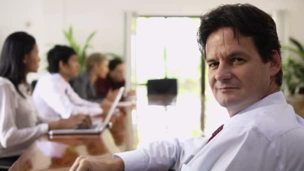 zralý muž, pracující jako manažer a při pohledu na fotoaparát během obchodního jednání