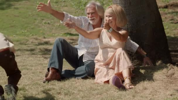 Seniors smiling with child and sitting on grass under tree. Slow motion