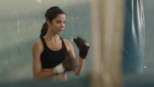 Pretty young hispanic woman training at boxing in gym