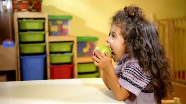 holčička jíst zelené jablko ve škole