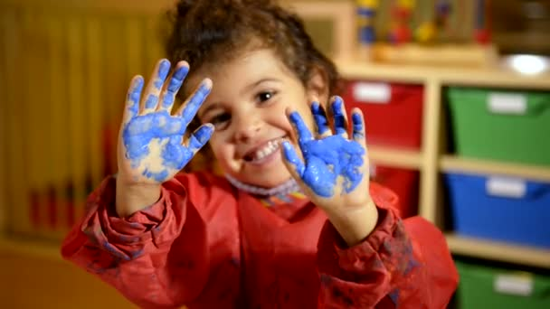 Happy children having fun and painting with hands in kindergarten.