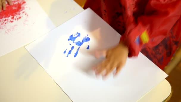 Happy children having fun and painting with hands in kindergarten