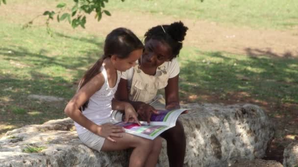 Children and education, female friends reading book in park