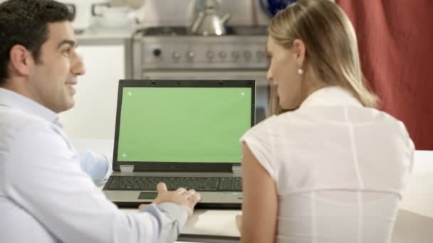 Young man and woman using laptop pc with green screen for internet and email at home.