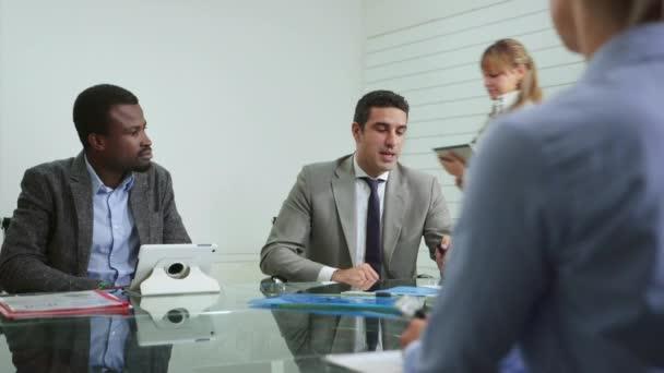 tým obchodních lidí pracujících v kanceláři salonek