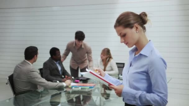Portrait of woman with business people in office meeting room
