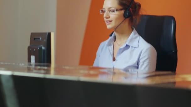 operátorek v hotelové recepci mluví po telefonu